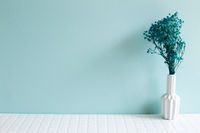 Vase of baby's breath, gypsophila dry flowers on white mosaic tile table. blue wall background. Home interior