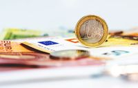 A used 1 euro coin standing on top of some euro banknotes