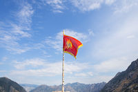 Montenegro flag against the background of a beautiful blue sky with clouds fluttering in the wind.