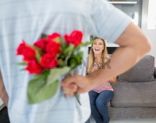 Man hiding bouquet of roses from smiling girlfriend on the couch