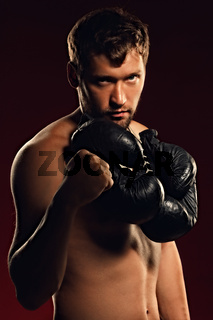 Portrait of a confident fighter on a dark background with a straight and bold look.