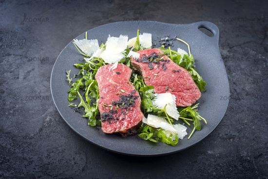 Modern style traditional fried New York strip steak with rucola and parmesan offered as close-up on a design plate