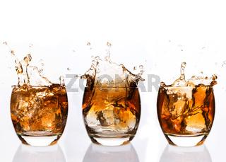Serial arrangement of whiskey splashing in tumbler
