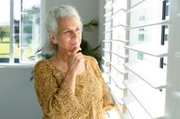 Thoughtful caucasian senior woman standing at window, looking into distance