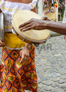 Tambourine player with a woman in typical clothes dancing in the background