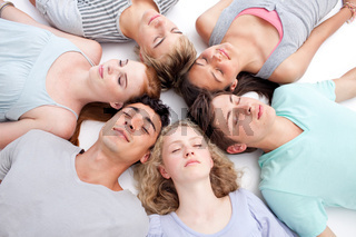 Teens sleeping on floor with heads together