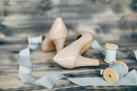 Blue silk ribbons on spools with the bride's beige shoes.