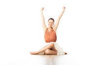 Cheerful young sporty attractive woman in bright white yoga studio, feeling exited, rising hands up in the air. Healthy active lifestyle