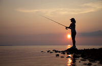 Woman fishing on Fishing rod spinning in Finland at sunset.