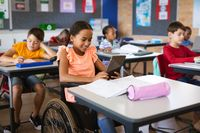 Disabled african american girl using digital tablet while sitting on wheelchair at elementary school