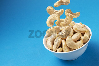 Falling cashew nuts into bowl on blue background, top view