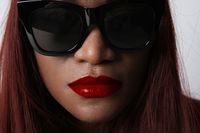 Close-up of black African young woman with red lips, wears sunglasses. Isolated.