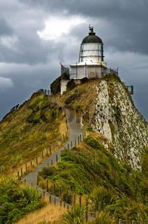 Nugget Point Leuchtturm in dunklen Wolken am Himmel, Catlins, Neuseeland