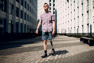 Disabled young man with foot prosthesis walks along the street