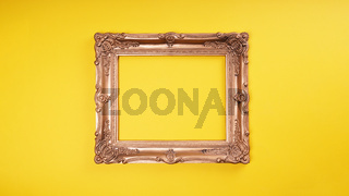empty ornate gold picture frame on yellow wall background