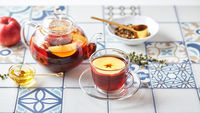 Fruit tea with apples and thyme in glass teapot and cup on table made of colored tiles