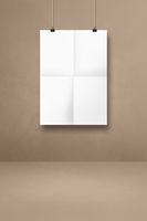 White folded poster hanging on a beige wall with clips
