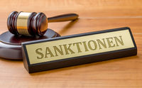A gavel and a name plate with the engraving Sanctions in german - Sanktionen