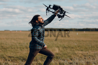 Man pilot holding quadcopter drone in hands at outside field.