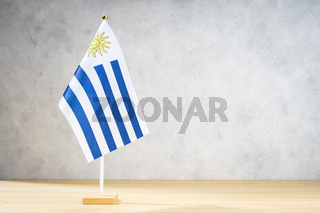Uruguay table flag on white textured wall. Copy space for text, designs or drawings