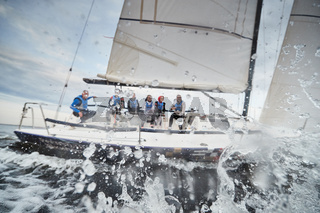 Russia, St.Petersburg, 05 September 2020: Participants of a sailing regatta on the sailboat, pull ropes, water splashes in the foreground, focus on splashes