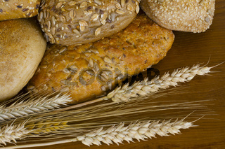 Vollkorn-Brötchen mit Getreideähren im Vordergrund