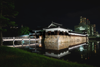 The illuminated Hiroshima castle with bridge surrounded by water in the night, Hiroshima, Japan