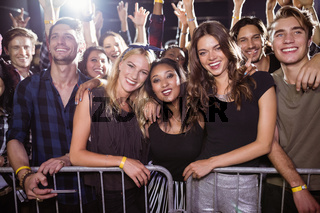 Portrait of happy friends at nightclub during music festival