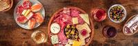 Italian antipasti or Spanish tapas panorama. Gourmet cold meat and cheese