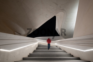 Unrecognized person walking at the stairs leading to a bright open space.