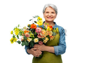 smiling senior woman in garden apron with flowers