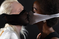 Caucasian and african american young woman isolated on black background.