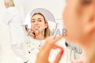Patientin blickt in den Spiegel vor Facelift