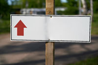 Signpost with directional arrow on a path at a campsite