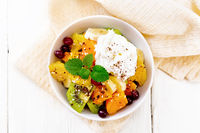 Salad fruit with cranberries and cream in bowl on board top