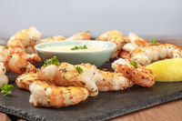 A closeup photo of plate of cooked shrimps with a sauce