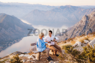Couple sits on a bench and drinks tea against the backdrop of Mount Lovcen and the Bay of Kotor