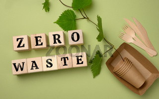 wooden cubes with an inscription zero waste and paper plates and disposable cups. The concept of avoiding plastic dishes