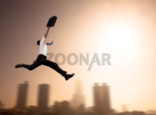 excited Businessman running with cityscape background at morning