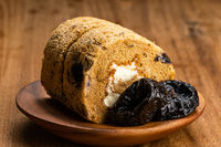 Closeup view of homemade prune sponge cake roll and dried pitted prune fruits in wooden plate.