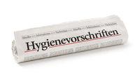 Rolled newspaper with the headline Hygiene regulations in german - Hygienevorschriften