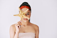 Pretty young afro woman covering her eye with starfish