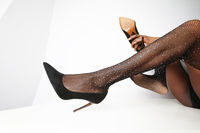 Cropped image of female legs with black high heels black shoes. Isolated.