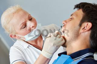 Zahnarzt sucht nach Karies bei Patient