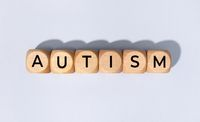 Autism word on wooden block isolated on gray background