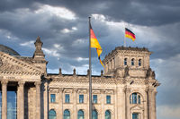 Facade Reichstag building Berlin with german flag and threatening air
