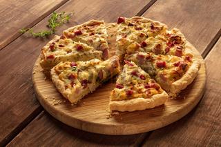 A photo of a quiche lorraine with thyme on a ustic wooden background