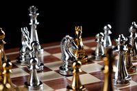 Gold and silver chess figures on chessboard