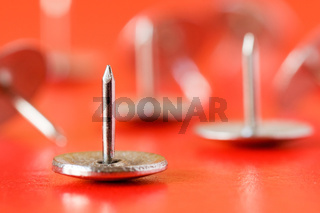 drawing pins on red background