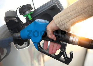 Mans hand refilling the car with a gas pump